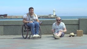 Two Men Listen To Music On The Embankment. Slow motion shot of a two men listening music together when seated on the embankment. One of them on wheelchair stock footage
