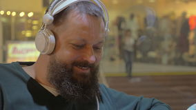 Two men listening to music in shopping mall. Close-up shot of two cheerful mature bearded men listening to music in headphone in shopping centre stock video