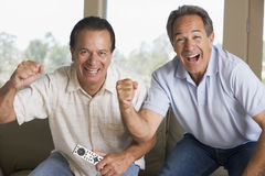 Two men in living room cheering Stock Image