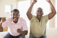 Two men in living room cheering and smiling Stock Photo