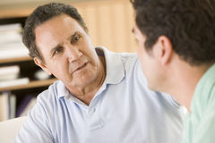 Two men in living room talking Stock Photo