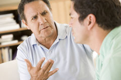Two men in living room talking Royalty Free Stock Image