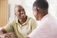 Two men in living room talking and smiling Stock Photo