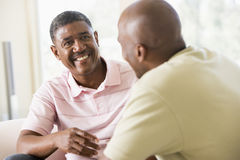 Two men in living room talking and smiling Royalty Free Stock Photography