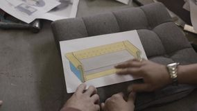 Two men look at drawing sofa and discuss it in furniture factory stock video footage