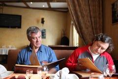 Two men look menu Royalty Free Stock Photography