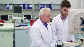 Two men look at the monitor at the laboratory. Two men in white coats look at the monitor at the laboratory. Mature scientist and his young intern working at the stock video footage