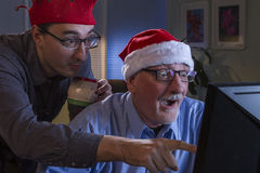 Two men look surprised while looking at computer during holiday season, horizontal Stock Image