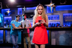 Two men looking at a beautiful woman. Two men looking at a beautiful women in bar Royalty Free Stock Photos