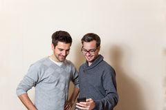 Two men are looking on a cell phone Royalty Free Stock Photos