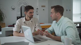 Two men looking at the computer discuss business project. Young handsome caucasian male sitting at the workplace. Businessman working at creative office stock footage
