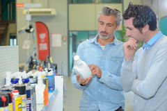 Two men looking at label mechanical product Stock Photos