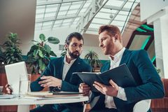 Two men looking at laptop screen in office. Royalty Free Stock Photography