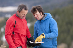 Two Men Looking at Map in the Wilderness. Two men stand and look down at a map together in the wilderness. One man is pointing at a spot on the map and talking Royalty Free Stock Photography