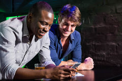 Two men looking at mobile phone and smiling at bar counter Royalty Free Stock Photos
