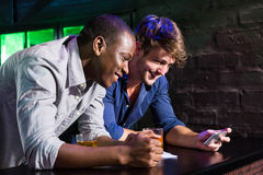 Two men looking at mobile phone and smiling at bar counter Stock Photo