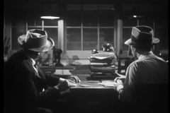 Two men looking through window at  train passing, 1940s stock video