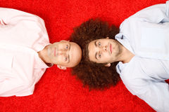 Two men lying on red carpet Stock Image