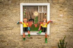 Two men made from plant pots sat in a window. stock image