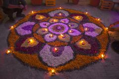 Two men make a mandala of flowers with burning candles in the evening of the festival of Diwali. Rangoli