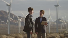 Two men making projects near the windmills stock footage