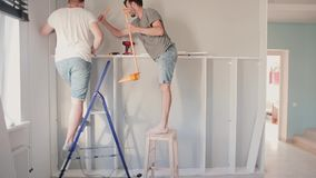 Two men making repair in the bright room. Man helping to his friend moving to new house, assemble furniture together. Two young men making repair in the bright stock video footage