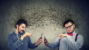 Two men manipulating internet with smarpthones. Exchanging with multiple ideas and thoughts Royalty Free Stock Photos