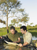 Two Men With Map Against Lake Royalty Free Stock Photography