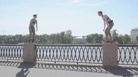 Two men in marine uniform sit on knee on postament at seafront, stand up together, weird. Surrealism. Water, summer sunny day stock video footage
