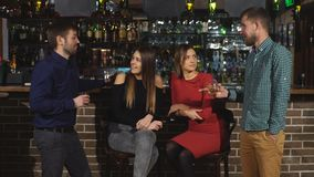 Two men meet in a bar. Two men flirting with two women stock video footage