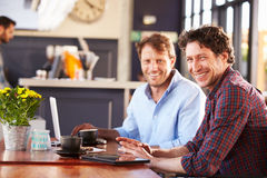 Two men meeting at a coffee shop, portrait Royalty Free Stock Photo