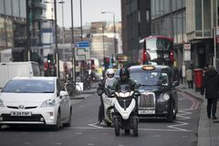Two men on motor scooters are driving along the road. London, UK - December 22, 2017: Two men on motor scooters are driving along the road Royalty Free Stock Photo