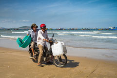 Two Men On A Motorbike By The Beach. Two men ride a motorbike on the shore of Mui Ne, Vietnam, on a sunny afternoon. They carry containers from the fish market Royalty Free Stock Photography