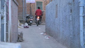 Two men on motorcycle driving through small alley in Jodhpur. JODHPUR, INDIA - 5 FEBRUARY 2015: Two men on motorcycle driving through small alley in Jodhpur stock video footage