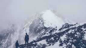 Two Men on Mountain With Snow Covering Surface and Clouds Covering Visibility Royalty Free Stock Photo