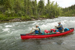 Adventure river rapid canoeing in wild Alaska royalty free stock photo
