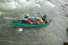 Two men in packed canoe on wild river rapids Royalty Free Stock Photo