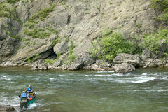 Two men navigate a rocky river in remote Alaska. Two men navigating a rocky river by canoe during an adventure in remote, wild Alaska Royalty Free Stock Photo