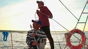 Two men navigating yacht at sunset, friendship, sailing, sport. Stock footage stock video footage