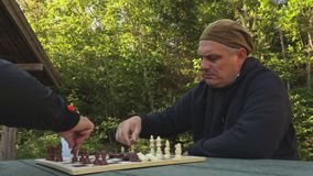 Two men near chessboard at outdoor. In summer day stock footage