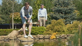 Two men near the pond feeding the fishes. Slowmotion. Two attractive men are in the blooming garden near the pond. Young pretty man stands on the stone and stock video footage
