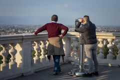 Two men observe the city of Vicenza with binoculars royalty free stock photography