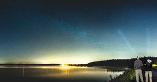 Two men observing beautiful Milky Way shining over lake. Panorama of two men with flashlights standing near lake, observing beautiful Milky Way shining above Royalty Free Stock Photo