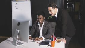 Two men in the office communicate in front of a computer. Two men in the office discussing the project in front of the computer stock video