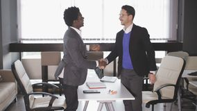 Two men in the office after the negotiations shake hands