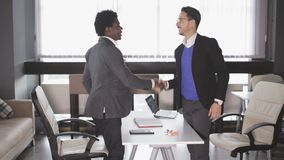 Two men in the office signed a contract and shake hands stock video