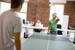 Two men in office space playing ping pong. With a women on the computer behind Stock Photo