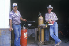 Two men at an old gas station Royalty Free Stock Photos