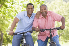 Two Men On Bikes Outdoors Smiling Royalty Free Stock Images