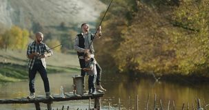 Two men and one little boy catching fish from lake with two fishing rod. stock video footage